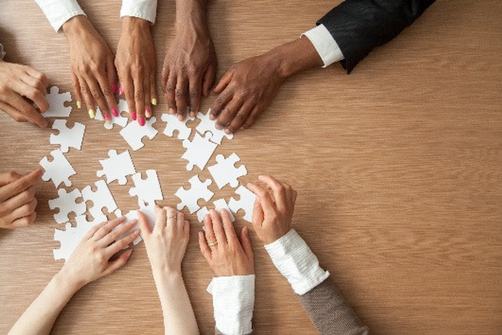 coaching_culture_strategic_imperative_diverse_hands_reaching_into_a_pile_of_white_puzzle_pieces_on_a_wooden_table_top_2.jpg